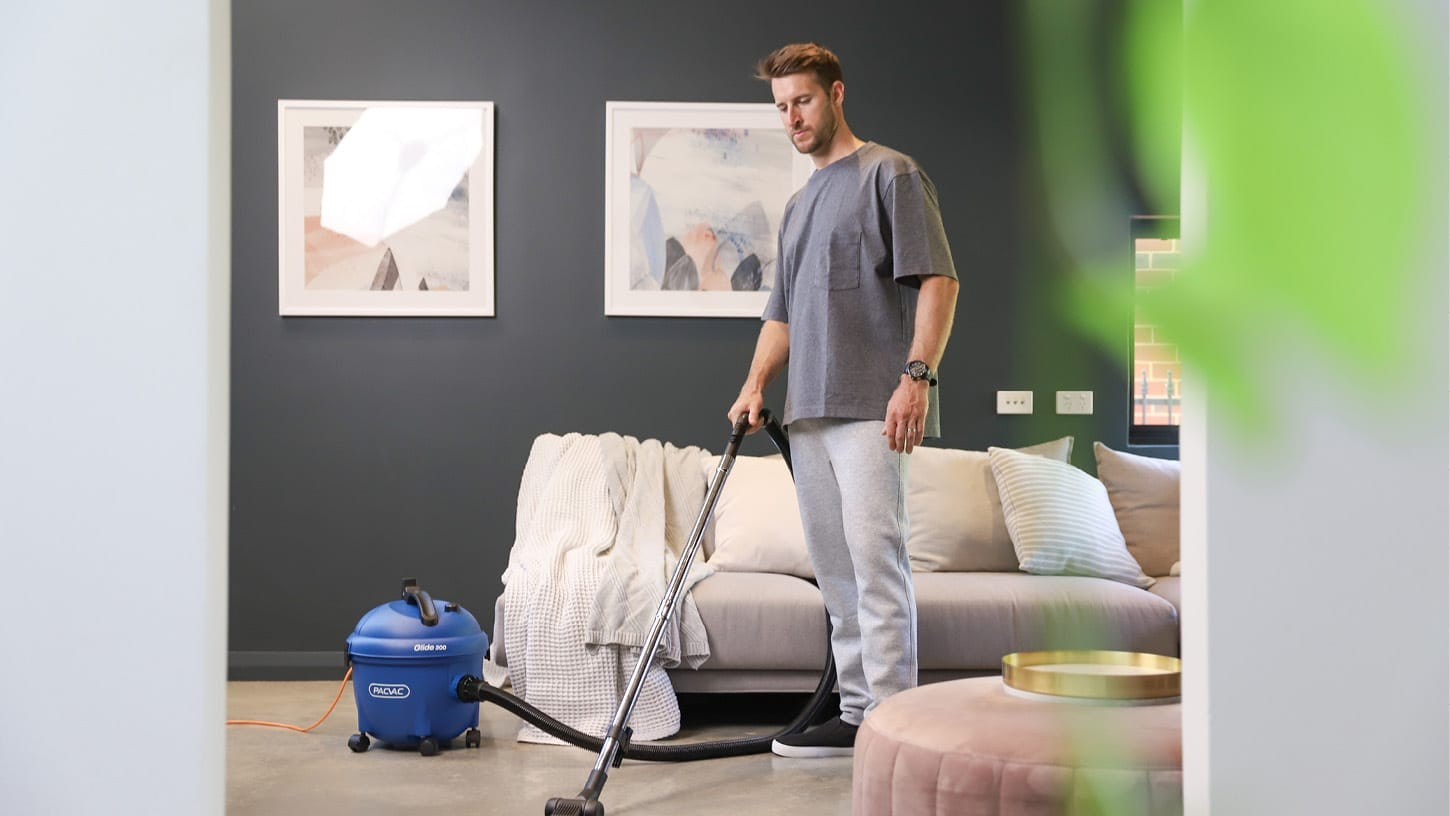 Male in comfortable clothing using a canister vacuum cleaner to vacuum the shiny floor of a living room, among modern looking furniture.