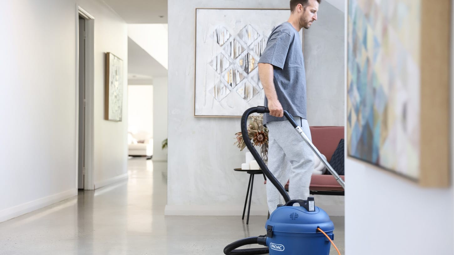 Young male in a comfortable outfit cleaning the bright hallways of a minimalistic residential home with polished concrete floors, with a commercial round blue canister vacuum.