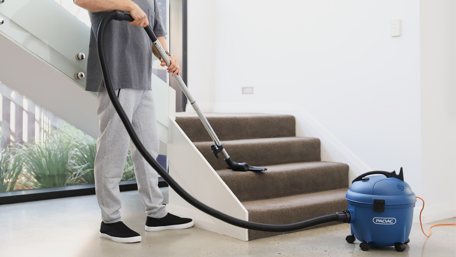 Person using a Glide wispa 300 canister vacuum to clean a carpeted staircase in a bright residential home with large windows.