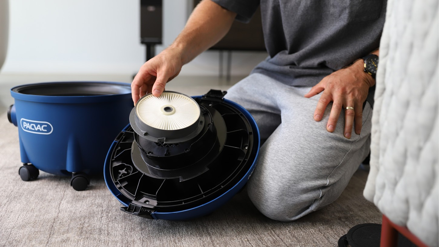 Photo of a person kneeled on the ground comfortably replacing the pre-motor HEPA rated filter of a Pacvac commercial canister vacuum.