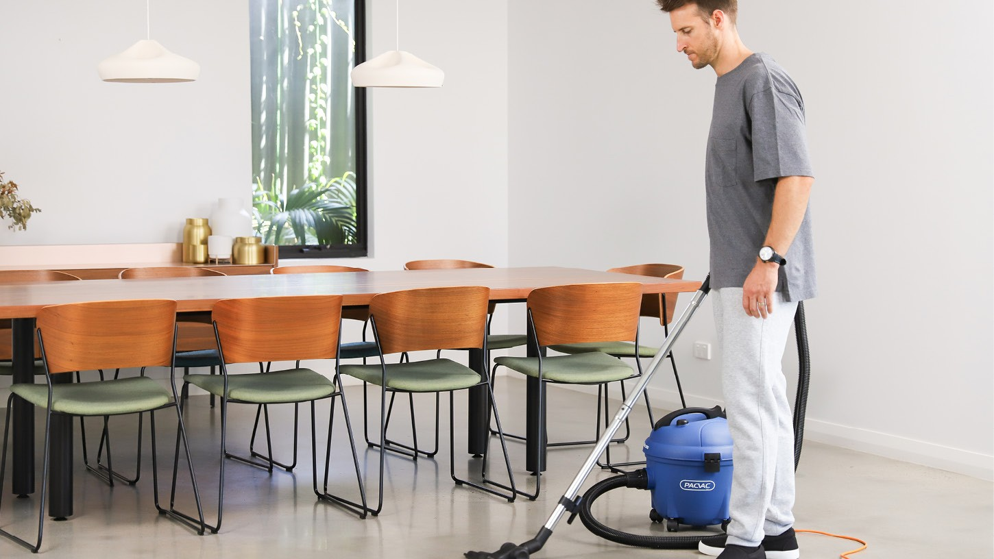 Man using a corded canister vacuum cleaner to vacuum the polished floors of a dining area in a bright residential home with a modern dining set.