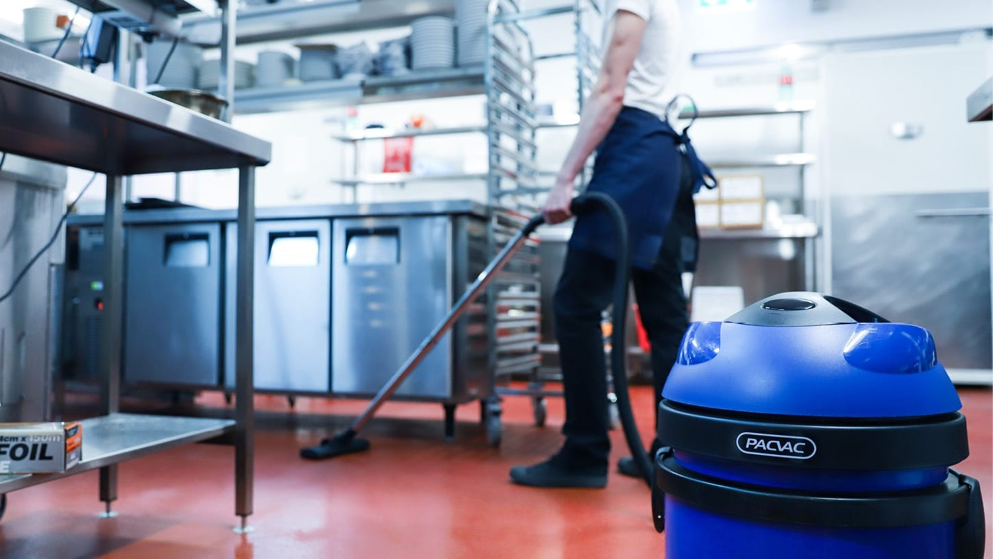 Hospitality worker using a commercial Pacvac vacuum to clean the floor of an industrial kitchen of a large restaurant.