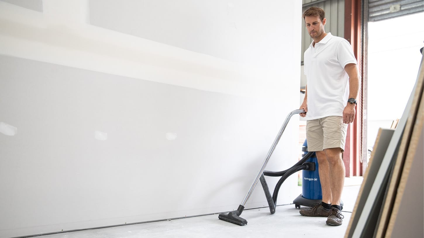Male in casual clothing using a commercial wet and dry vacuum to clean the concrete floor of a warehouse, where construction is happening with wooden panels.