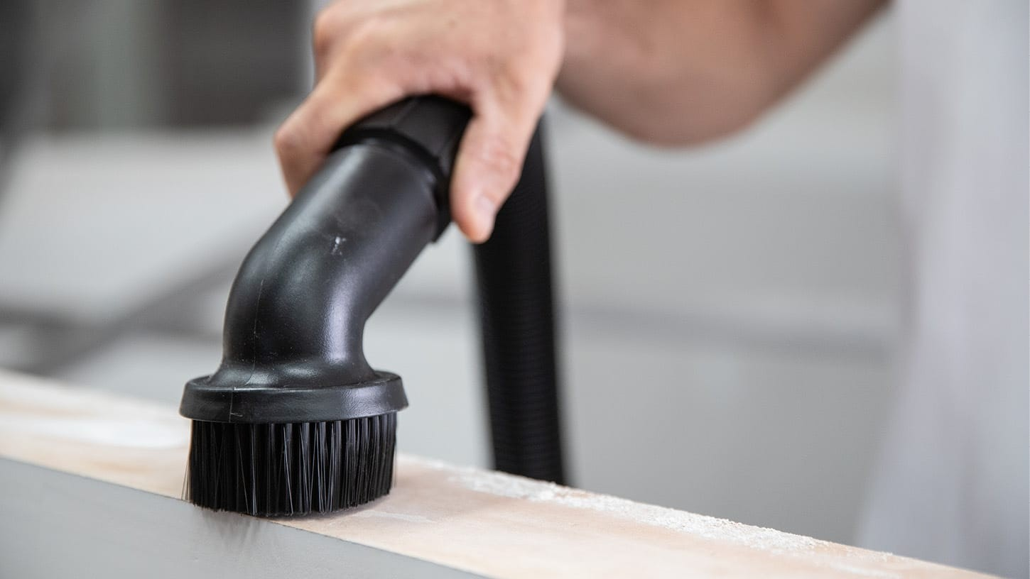 Close-up photo of a dusting brush accessory being used to suck up sawing dust, wood chips and wood particles.