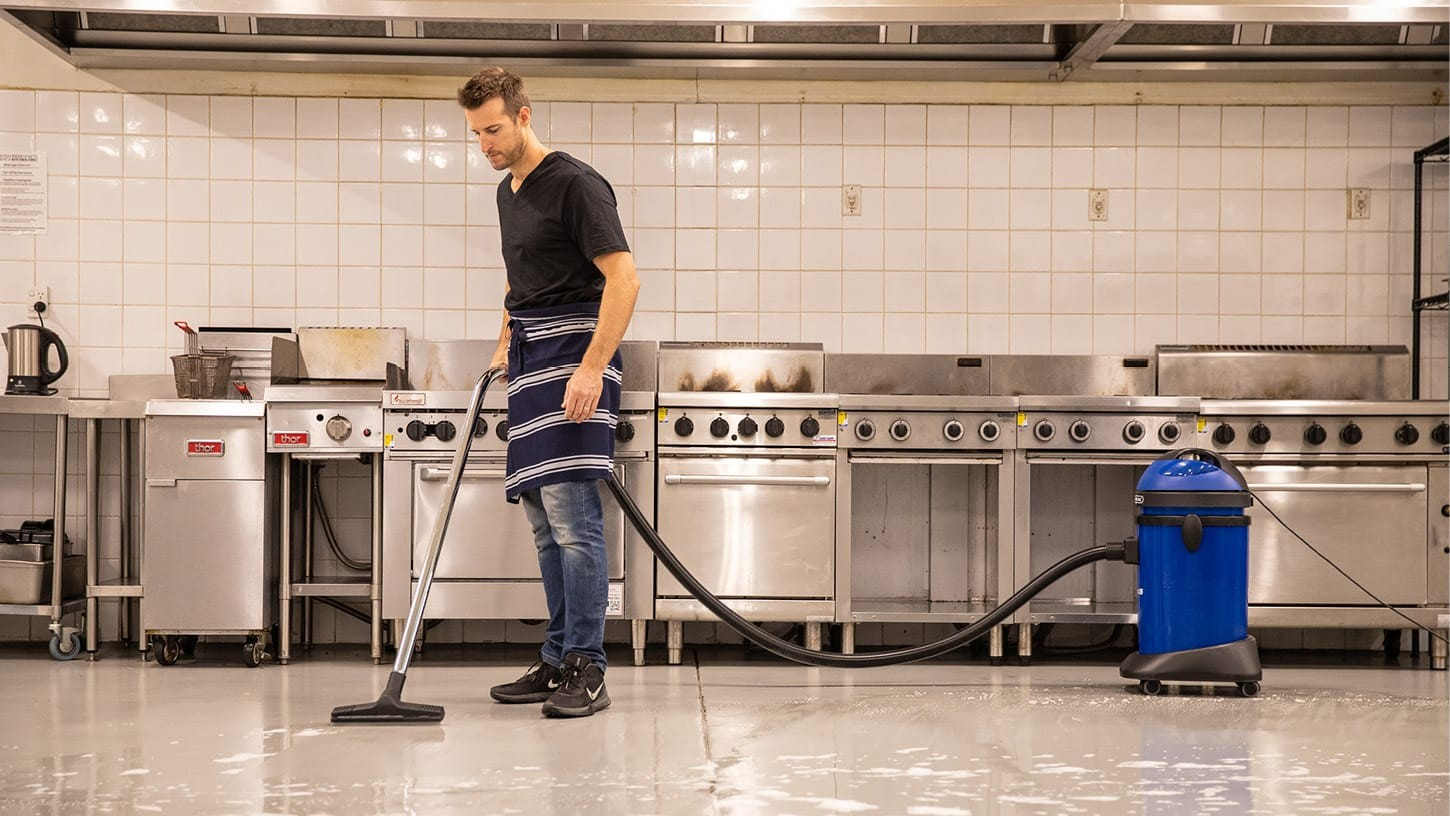 Hospitality worker using a Pacvac Hydropro 36 commercial wet and dry vacuum to clean the wet and soapy floor of a large industrial kitchen, with multiple steel stoves, grills and deep fryers in the background.
