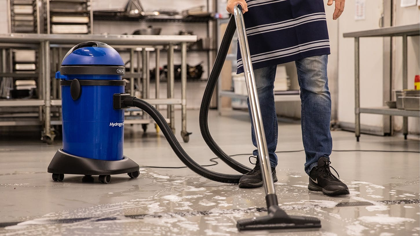 A blue Pacvac waterproof commercial wet and dry vacuum is being used to suck up soapy water from the floor of an industrial kitchen with metallic shelving.
