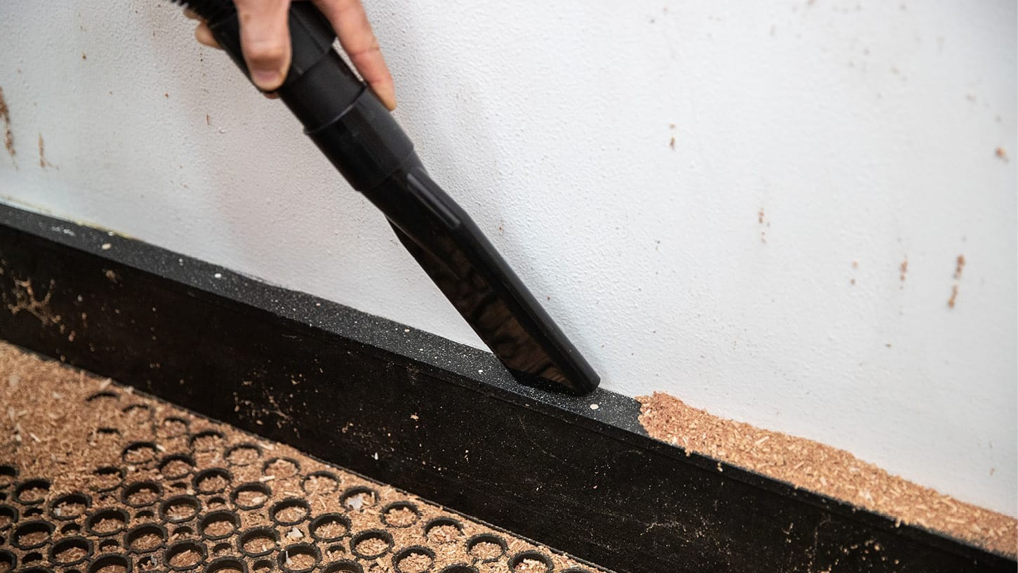Close-up photo of a crevice tool being used to suck up saw dust and wood chips along the floor and wall corner of a room.