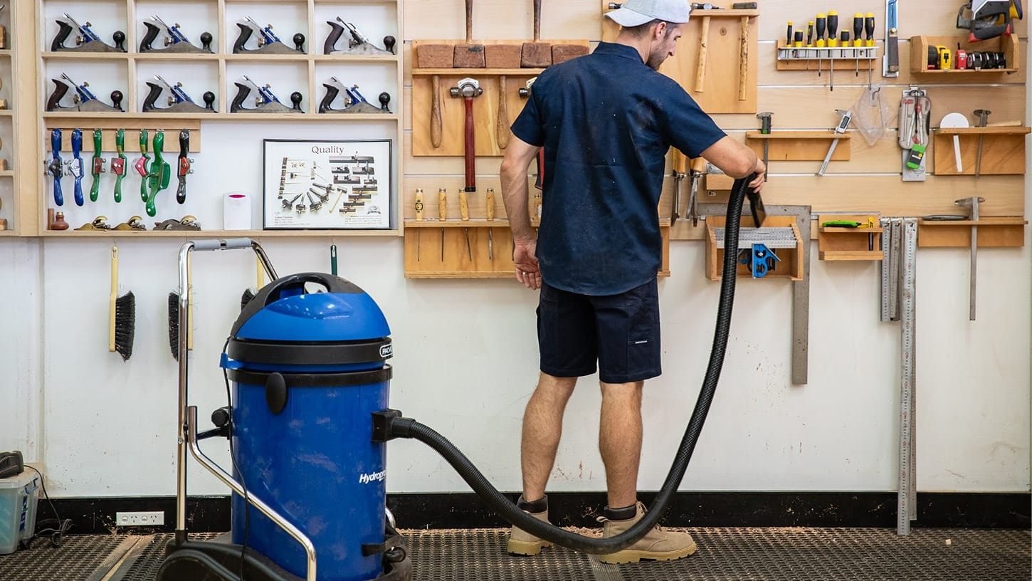 Young male with a baseball cap is using the crevice tool accessory of a Pacvac Hydropro 76 commercial vacuum cleaner to suck the sawdust off shelves and tools mounted against a white wall.