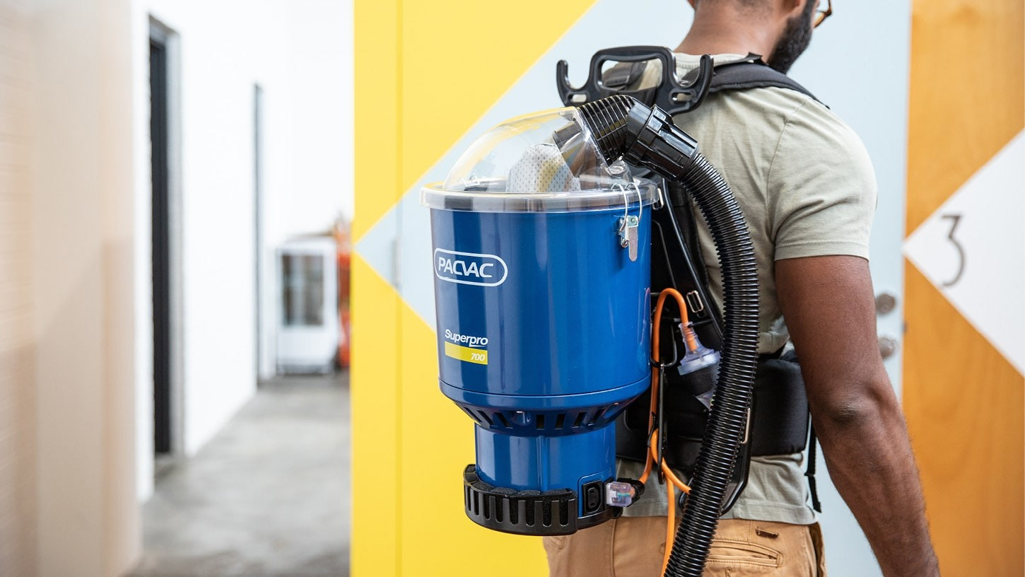 Close-up of the back of a person, cleaning a colourful and industrial looking office with a Superpro 700 corded backpack vacuum.