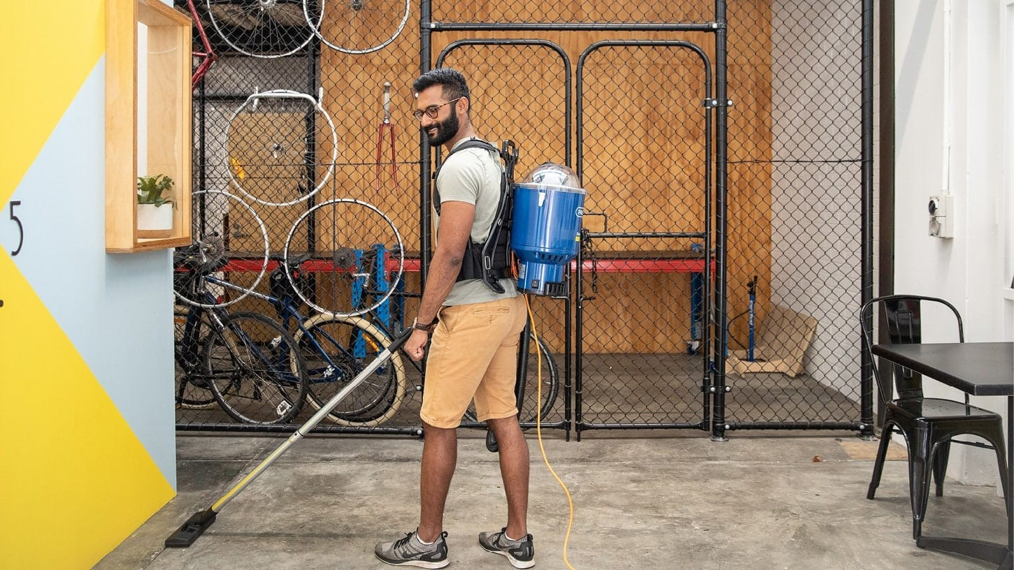Young male wearing t-shirt and shorts vacuuming the floor of a modern and industrial looking office space with a corded backpack vacuum, with a bicycle workshop in the background.