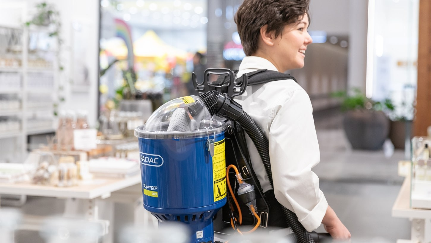 Close-up of the back of a young woman using a backpack vacuum cleaner in a well-lit up retail shop.