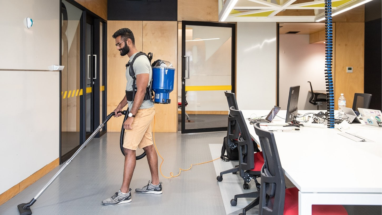 Young male vacuuming with a Superpro 700 corded backpack vacuum in an office space, around desks with computers.