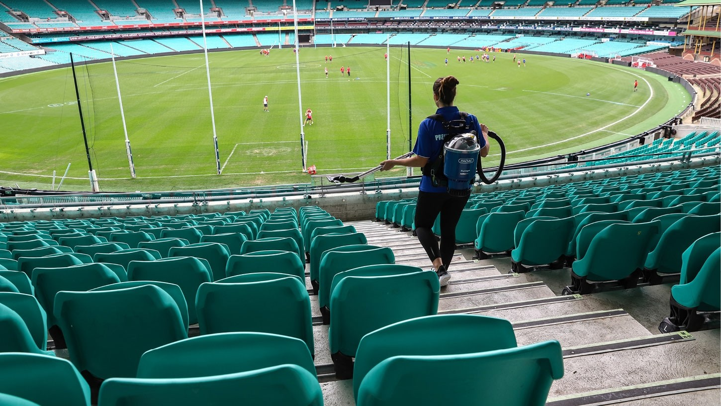 Woman walking down the steps of an Australian football stadium between the seating, with a cordless backpack vacuum.
