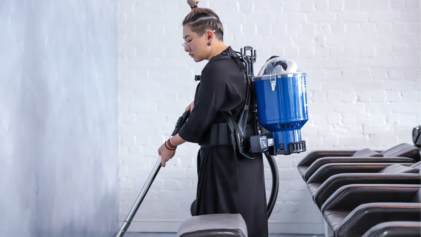 Side-shot of a woman vacuuming the floor of a bright hair salon with a battery backpack vacuum.