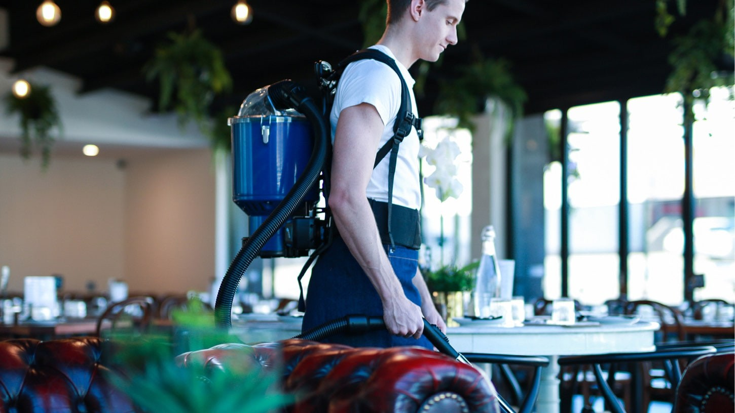 Hospitality worker using a Superpro battery 700 advanced cordless backpack vacuum in a restaurant preparing to open its doors.
