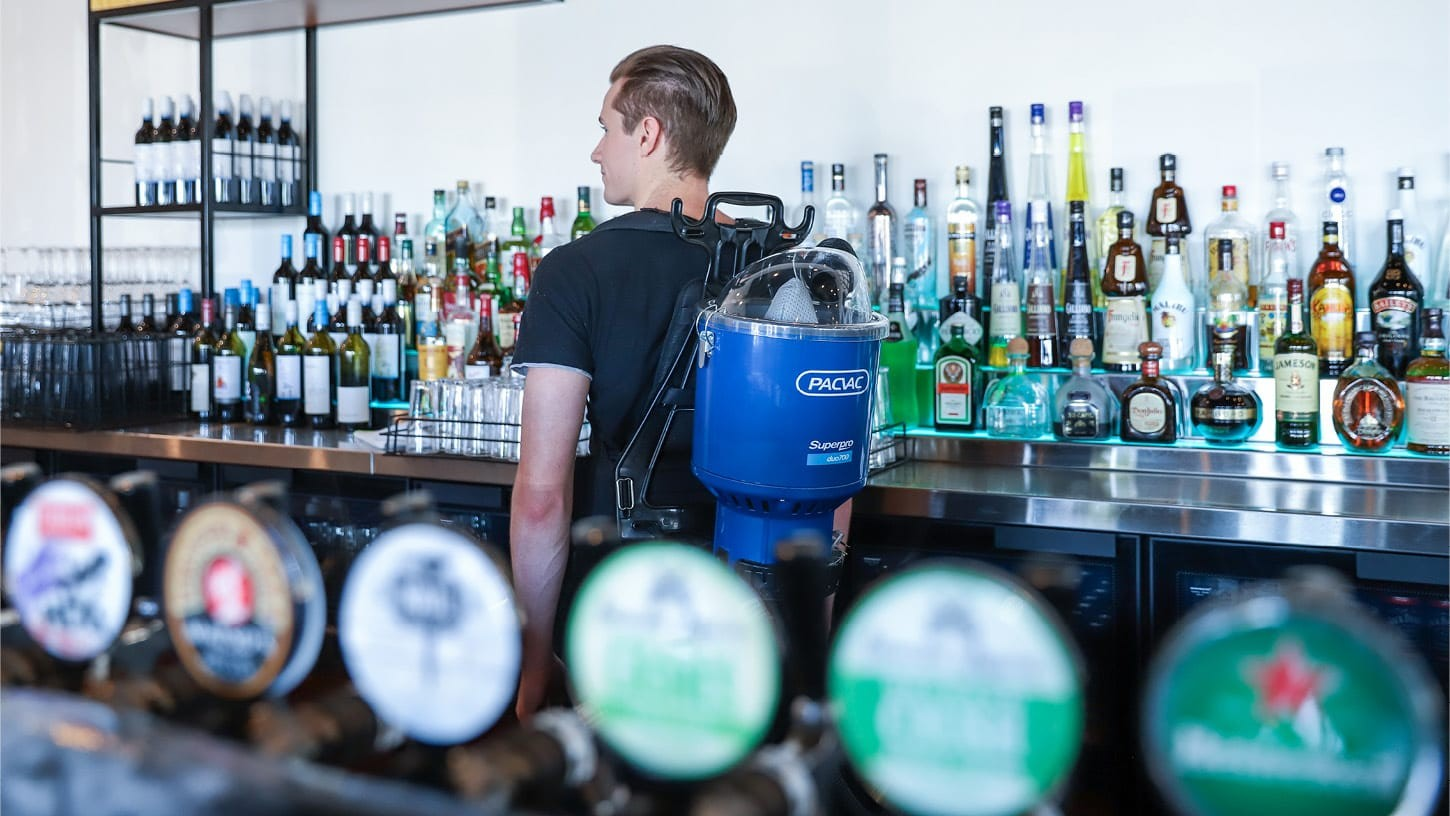 Young male behind a well stocked bar with lots of liquor wearing a Superpro duo 700 backpack vacuum.