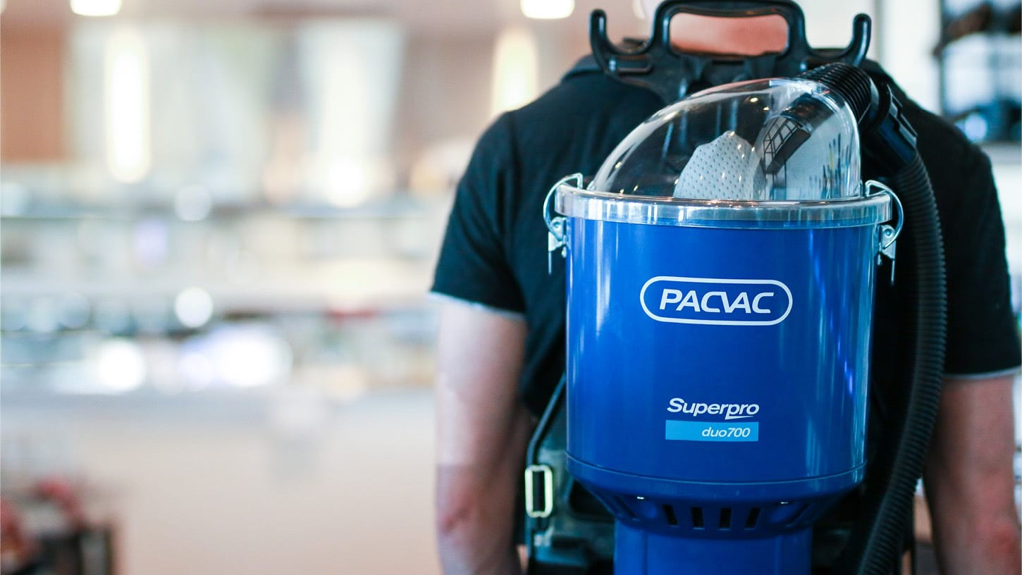 Close-up shot of a person wearing a Superpro duo 700 backpack vacuum.