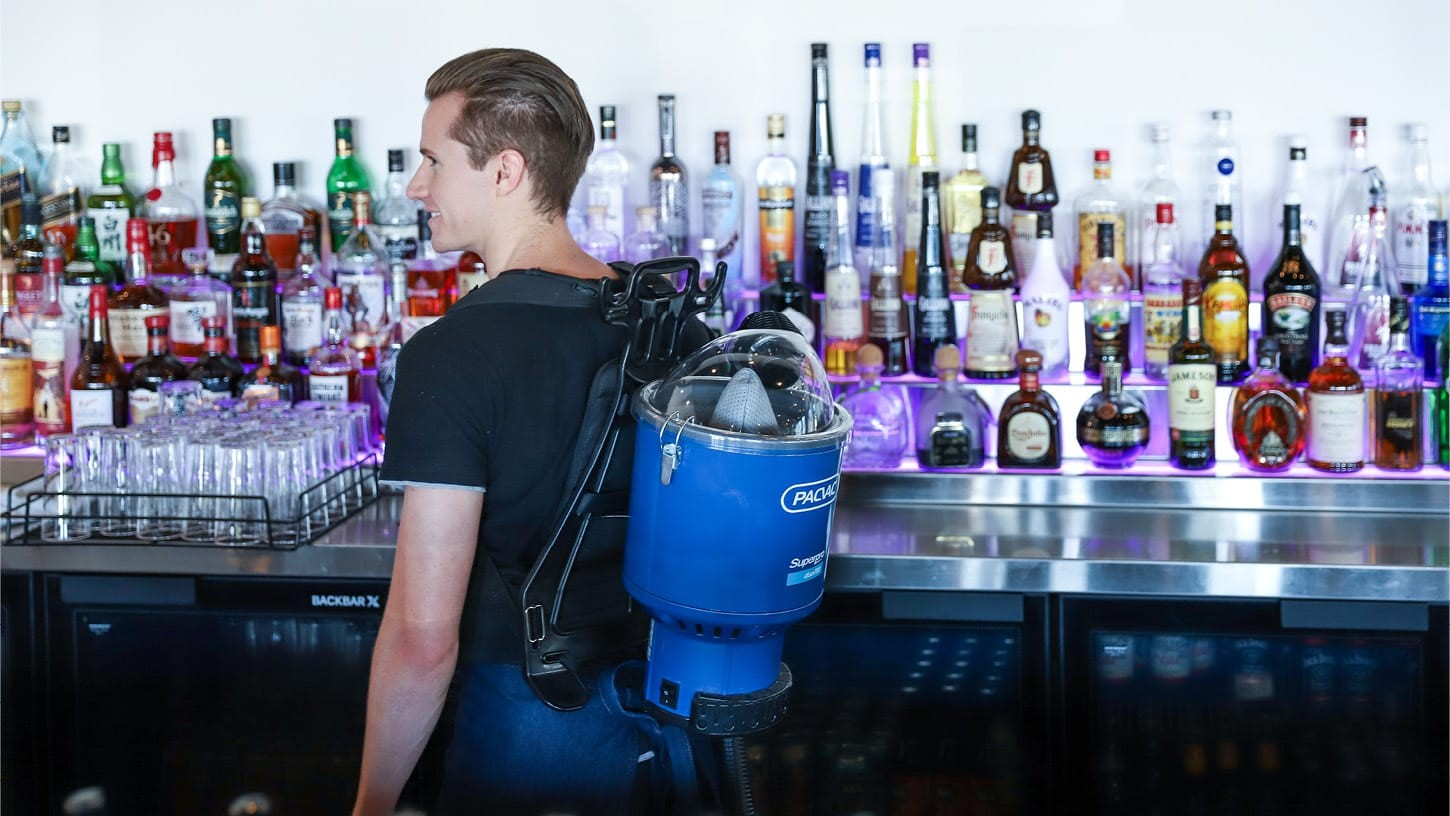 Male in a bar with lots of liquor and glassware using a water-proof backpack vacuum.
