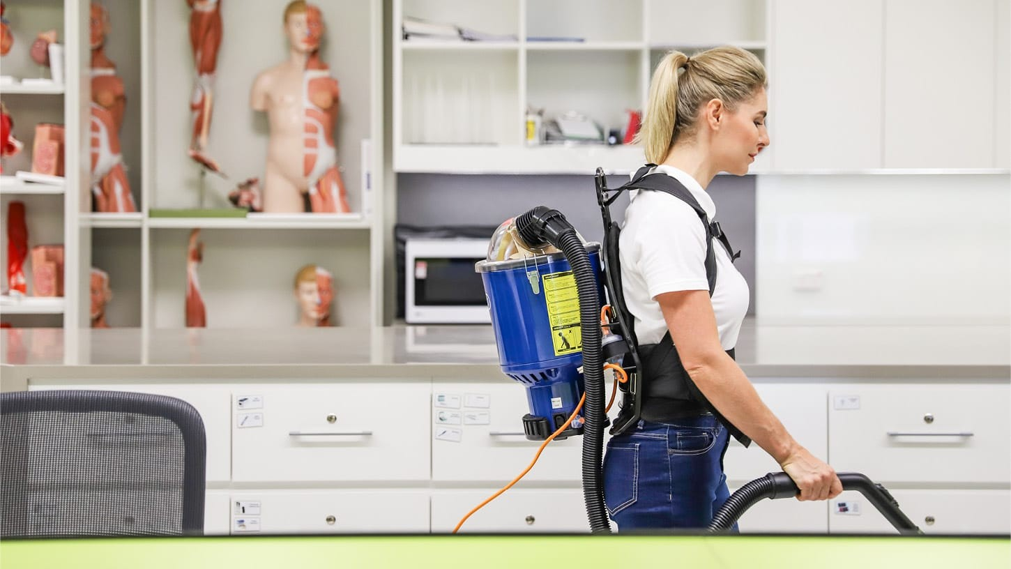 Young lady using a Superpro micron 700 backpack vacuum in the office of a physiotherapist, in front of shelves and drawers with human anatomical models.