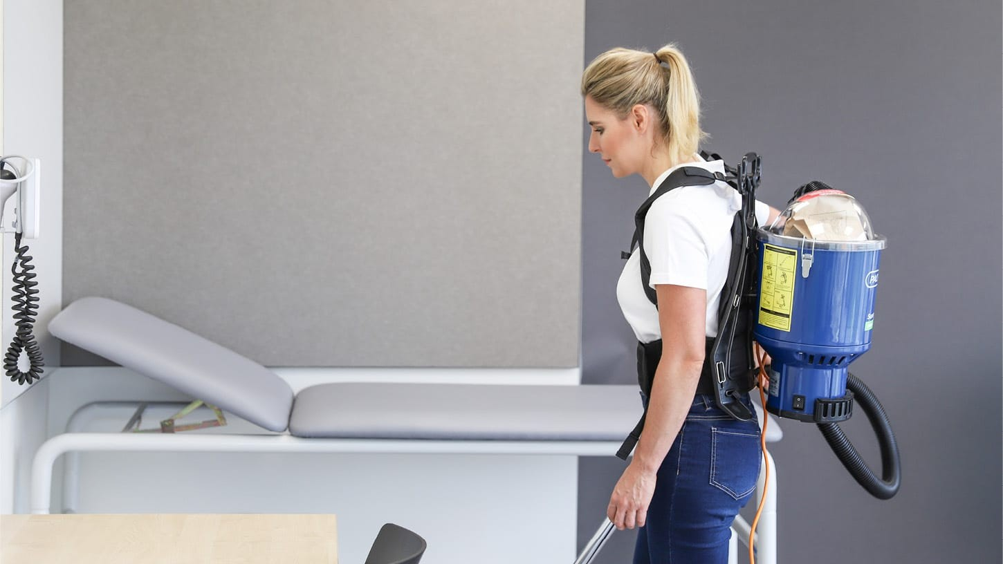 Cleaner using a HEPA rated corded backpack vacuum in a clean and luminous physiotherapists treatment room, in front of an examination couch.