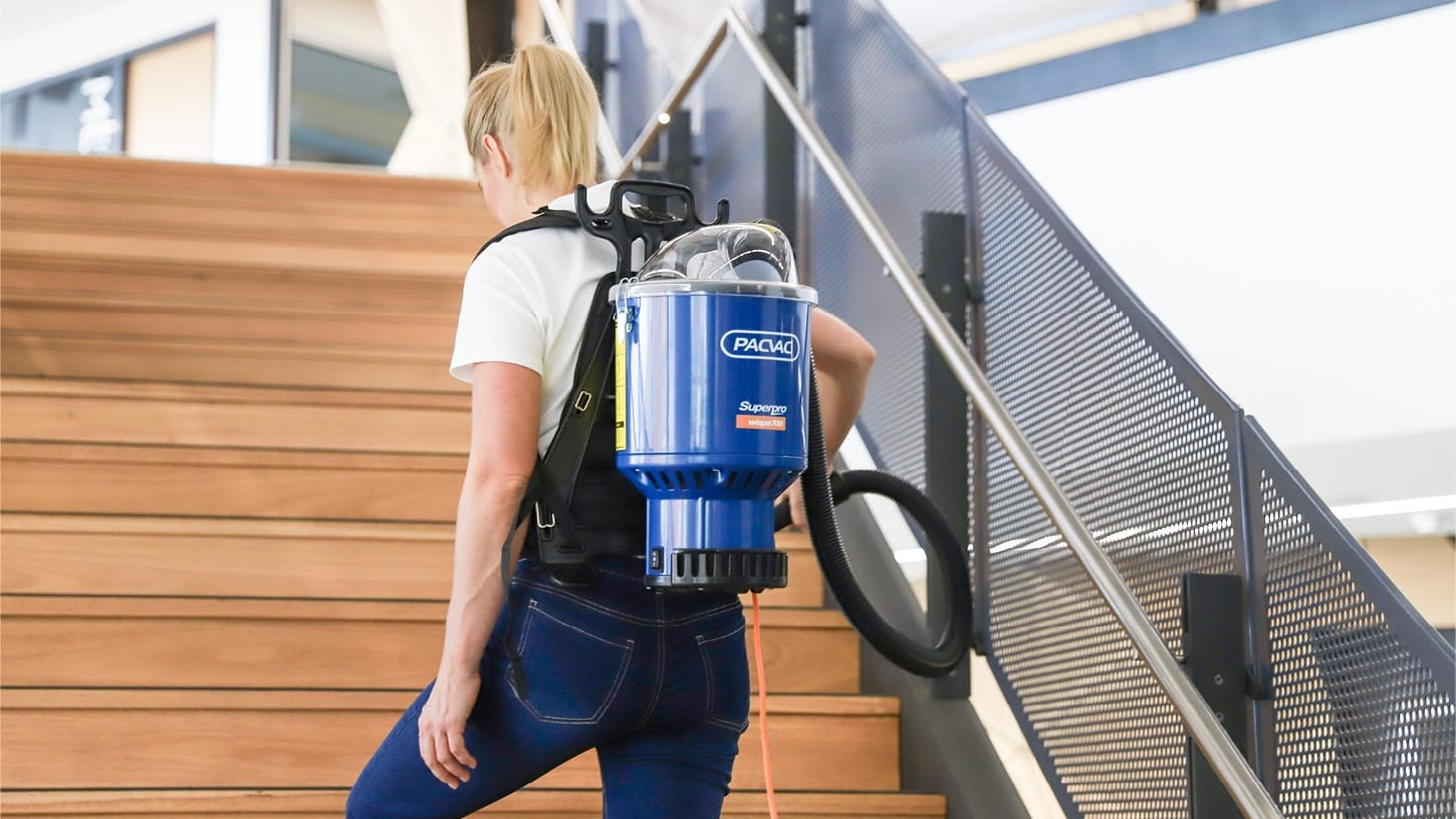 Cleaner in a university building vacuuming large steps of a stairs with a Superpro wispa 700 backpack vacuum.