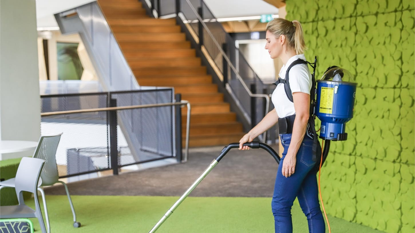 Lady vacuuming the carpeted floor of a large school with multiple levels with a corded backpack vacuum.