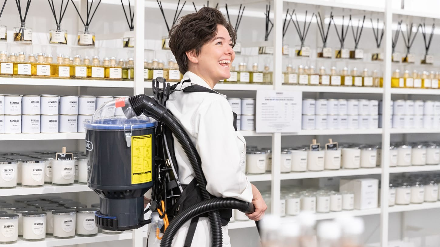 Young woman smiling as she vacuums with a Thrift 650 corded backpack vacuum in a retail shop, in front of shelves with scented candles and oil diffusers.