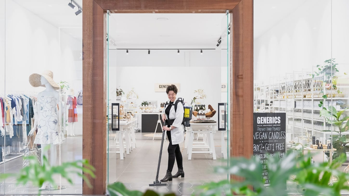 Photo of the storefront of a boutique retail shop called Generics, with large glass windows and shop assistant smiling as she's vacuuming the floor with a backpack vacuum.