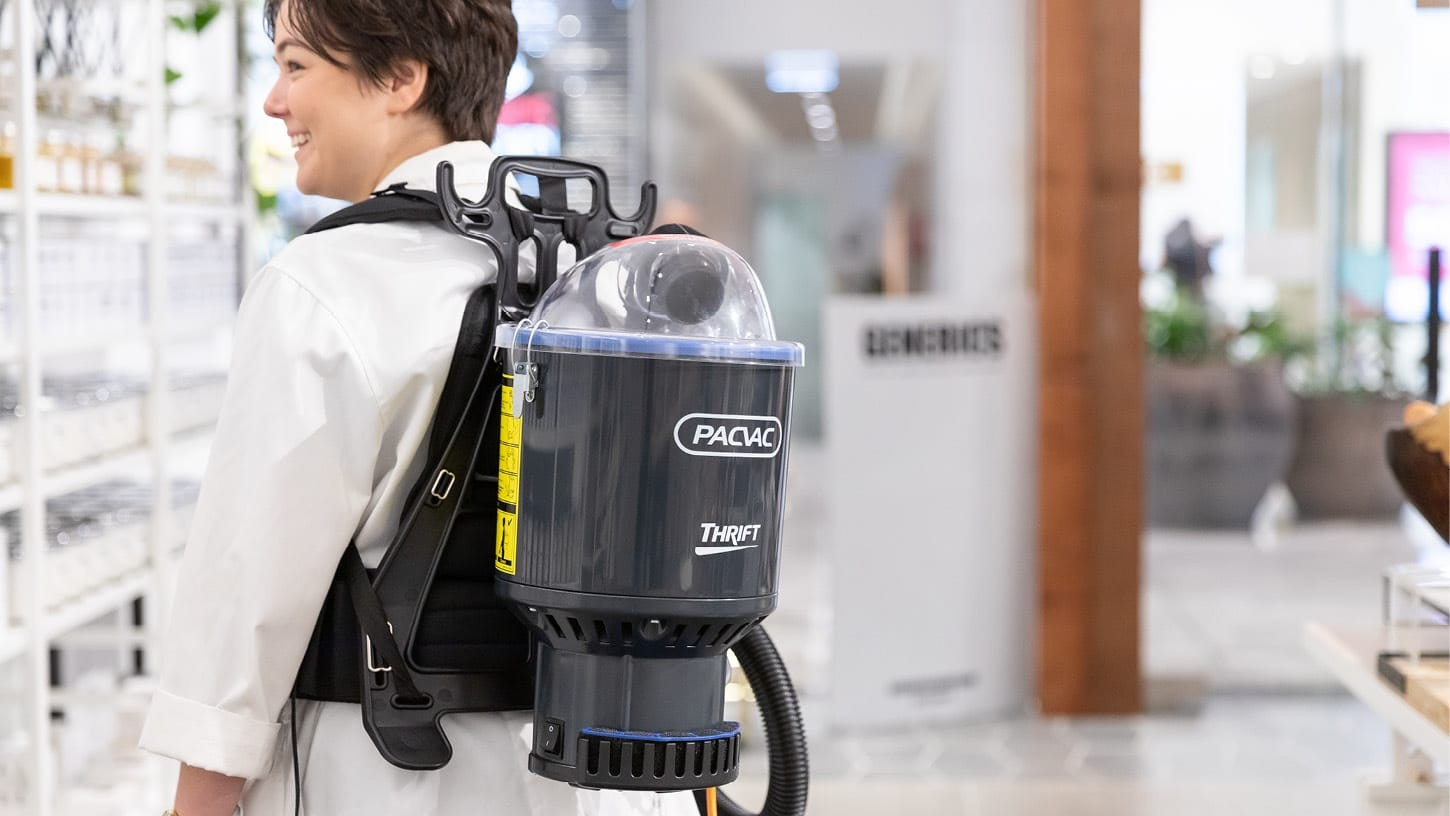 Close-up photo of the grey Thrift 650 backpack vacuum on the back of a young shop assistant, in a boutique retail shop.